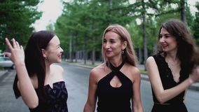 Three happy multi ethnic girls friends go to party nightclub walk city street. Slim multi ethnic young women in black attire enjoying friendship talking stock video footage