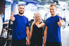 Three happy people at the gym showing thumbs up. royalty free stock photography