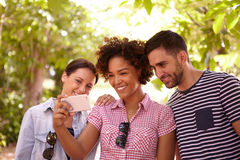 Three happy people smiling at cellphone Stock Photo