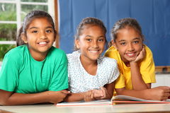 Three happy school girls reading a book in class. Three happy smiling young school girls sitting in a row in classroom reading a book together - Canon 5D MKII Stock Image