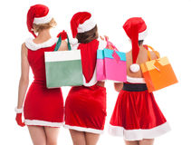 Three happy shopping girls holding bags and wearing Christmas ha Stock Images