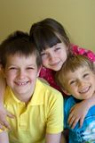 Three happy siblings. Three young, happy kids, all siblings, enjoying being together stock photo