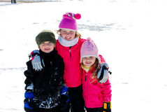 Three happy siblings in the snow on vacation. Two pretty girls and one cute boy huddled together smiling at camera Stock Photography