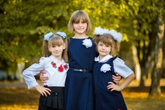 Three happy sisters hug in autumn park in school uniform together. Big family, happy together stock photos