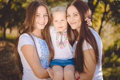 Three happy sisters hugging and smiling joyfully in summer park Royalty Free Stock Image