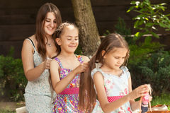 Three happy sisters plaiding hair at backyard Royalty Free Stock Photos