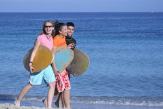 Three happy skim surfers. 3 surfers walking along edge of sea Royalty Free Stock Photography