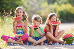 Three happy smiling child eating watermelon