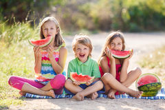 Three happy smiling child eating watermelon Stock Image