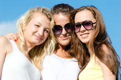 Three happy smiling girl friends embracing against blue sky. Closeup portrait of three happy young women teens embracing against blue sky on bright summer day Stock Image