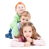 Three happy smiling kids lying on pile stack. Royalty Free Stock Photo