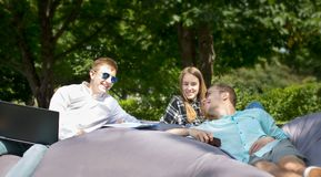 Three happy smiling young friends laying on a cushion outdoors a. Nd looking at each other. One guy has a laptop and another one is holding a cellphone stock photo