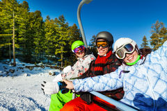 Three happy snowboarders sitting in elevator Stock Image