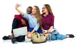 Three happy students with books, laptop, bags and makes selfie Stock Photography
