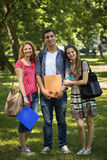 Three happy students in front of the campus. This is an image of a happy and smiling college students in a university campus Stock Images