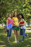 Three happy students in front of the campus Royalty Free Stock Images