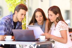 Three students learning together in a coffee shop. Three happy students learning together reading notes in a coffee shop royalty free stock photo