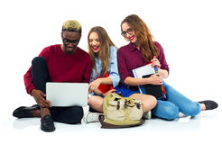 Three happy students sitting with books, laptop and bags royalty free stock photography