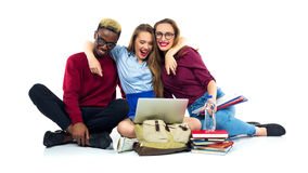 Three happy students sitting with books, laptop and bags Stock Photos
