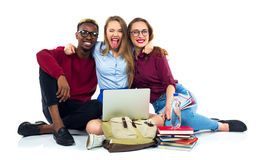 Three happy students sitting with books, laptop and bags Stock Photo