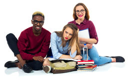 Three happy students sitting with books, laptop and bags Stock Image