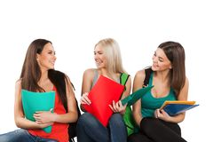 Three happy students sitting together with fun Stock Image