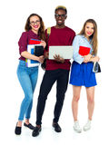 Three happy students standing and smiling with books Stock Photo