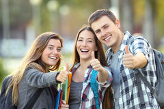 Three happy students with thumbs up. Three happy students looking at you with thumbs up in an university campus Royalty Free Stock Images