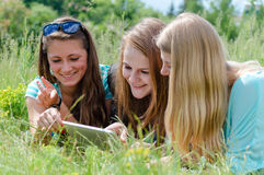 Three happy teen girl friends and tablet computer Stock Photography