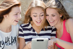 Three happy teen girl friends and tablet computer Royalty Free Stock Photography
