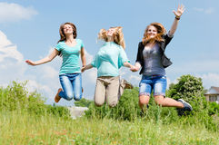 Three happy teen girls friends jumping high in blue sky. Three happy teen girls friends jumping high on green lawn against blue sky Royalty Free Stock Images