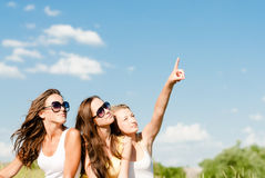 Three happy teenage girls showing up into blue sky copy space Royalty Free Stock Photos