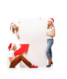 Three happy teenagers in Christmas hats pointing on a banner. Three happy teenagers in Christmas hats pointing on a large blank banner with arrows. The image is Royalty Free Stock Photos