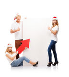 Three happy teenagers in Christmas hats pointing on a banner. Three happy teenagers in Christmas hats pointing on a large blank banner with arrows. The image is Royalty Free Stock Photo