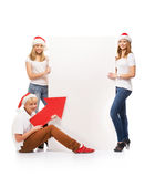 Three happy teenagers in Christmas hats pointing on a banner. Three happy teenagers in Christmas hats pointing on a large blank banner with arrows. The image is Royalty Free Stock Photography