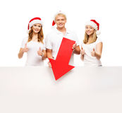 Three happy teenagers in Christmas hats pointing on a banner. Three happy teenagers in Christmas hats pointing on a large blank banner with a red arrow. The Stock Image