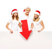 Three happy teenagers in Christmas hats pointing on a banner. Three happy teenagers in Christmas hats pointing on a large blank banner with a red arrow. The Stock Photography