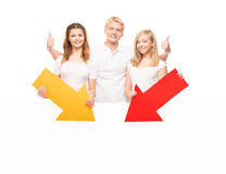 Three happy teenagers holding colorful arrows. Group of teenagers with a blank, white billboard isolated on white. The guys are holding arrows Stock Images
