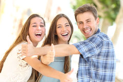 Three happy teenagers laughing with thumbs up Stock Photos