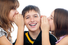 Three happy teenagers sharing a secret. Two smiling teenage girls sharing a secret with happy teenage boy stock photos