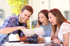 Three happy tourists checking guide in a coffee shop. Three happy tourists checking paper guide sitting in a coffee shop stock images