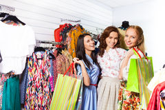 Three happy women with bags in shop Stock Photos