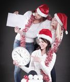 Three happy women in costume of Santa Claus with clock,and Chri. Happy women in costume of Santa Claus with clock, and Christmas shopping . on black stock image