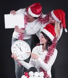 Three happy women in costume of Santa Claus with clock,and Chris. Happy women in costume of Santa Claus with clock, and Christmas shopping . isolated on black stock image