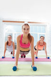 Three happy women doing plank together Stock Images