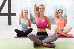 Three happy women doing yoga asanas in gym Royalty Free Stock Photos