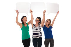 Three happy women holding blank speech bubbles over their heads Royalty Free Stock Image