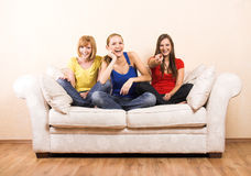 Three happy women on a lounge Stock Photo