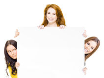 Three happy women with promotional sign. Three happy women full of femininity, vitality and zest peering round a large blank white promotional sign to attract Royalty Free Stock Images