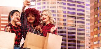 Three happy women on shopping. Afro american, asian and caucasian races. Black friday holiday. Concept for season sales. Beautiful young women make shopping in stock photos